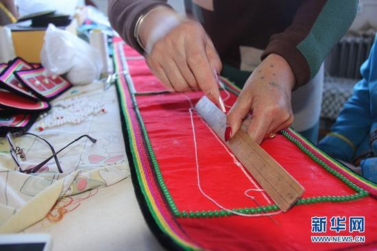 图为在手工作坊里,杨海燕的妈妈正在用划粉和木尺画线。
