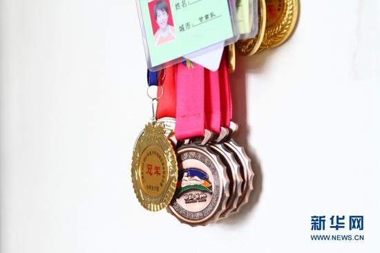 梦渊和姐姐获得的足球奖牌。新华网发(丁凯 摄)