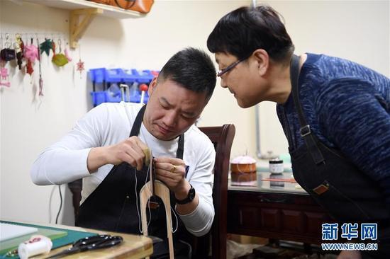李丽(右)在工作室指导顾客制作皮具(1月12日摄)。 新华社记者 范培珅 摄