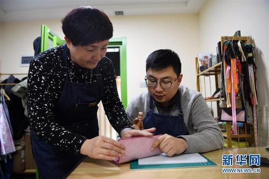 李霞(左)在工作室指导顾客打磨皮具(1月12日摄)。 新华社记者 范培珅 摄