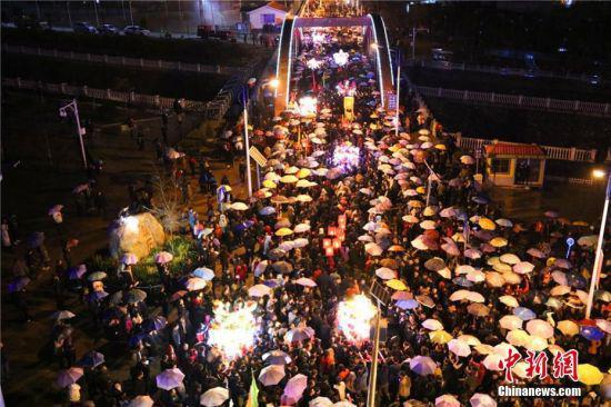 """图为当天,天空下起小雨,数万民众撑起雨伞和""""婆婆""""的圣辇一起行进。 全当周 摄"""