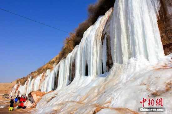 连日来,甘肃靖远县持续低温天气,其境内的河靖坪村的山层砂岩渗水后出现结冰现象,形成冰瀑奇观,吸引众游客和摄影爱好者观赏拍照。林志国 摄