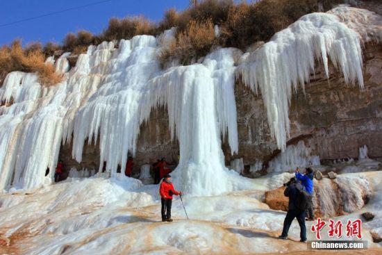 孩童在冰瀑前拍照留念。
