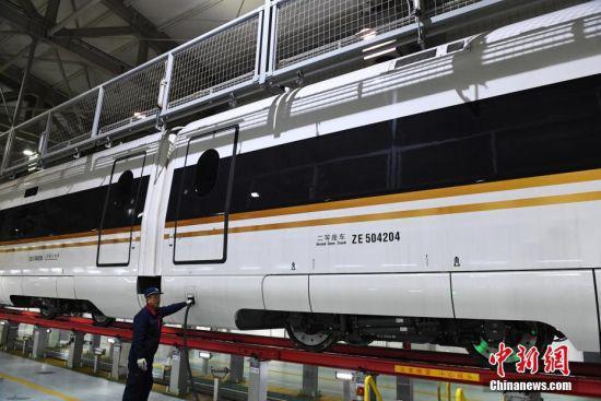 """2月23日晚,由兰州西开往广州南的G834次动车组列车在兰州西动车运用所进行检修,这是""""复兴号""""动车开进古丝绸之路重镇兰州参加的首个春运。 中新社记者 杨艳敏 摄"""