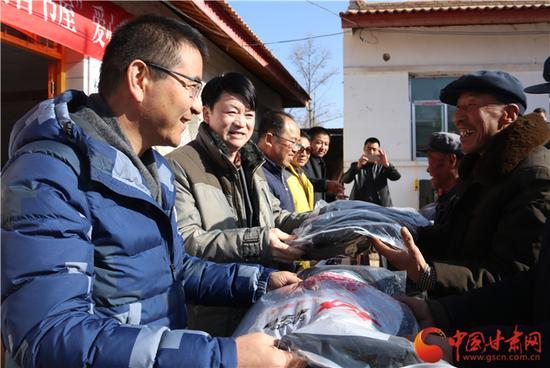 甘肃多识爱心基金会执行秘书长李兴江为乡亲们送新衣