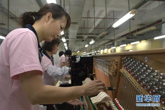 珠江钢琴集团的工人对立式钢琴进行音色整理(资料照片)。新华社发
