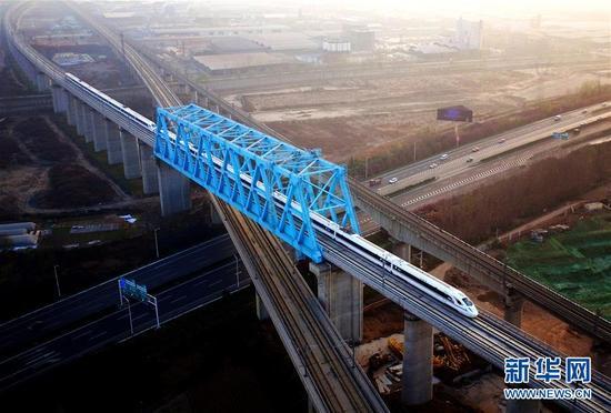 西成高铁由西安北站驶出的列车经过西成高铁跨西宝高铁特大桥(12月6日摄)。