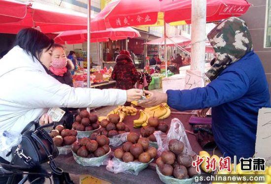 兰州城区市场上,居民购买冻梨。闫姣 摄