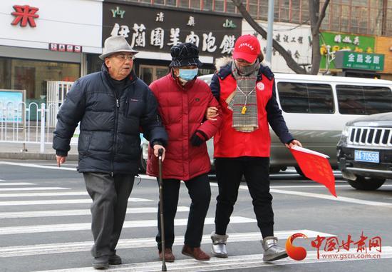 志愿服务队队员帮助老人过马路