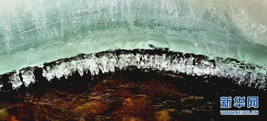 """这是2月22日在甘肃省张掖市肃南裕固族自治县拍摄的隆畅河风光。初春时节,气温逐渐回升,隆畅河冰雪开始融化,呈现出冰河""""两重天""""的景象,令人惊艳。新华网发(武雪峰 摄)"""