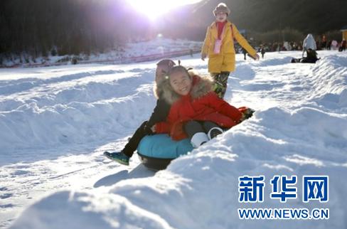 游客在甘肃省定西市渭源县渭河源景区内的冰雪游乐区玩耍