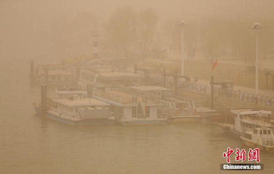 停靠在黄河兰州段岸边的船只在黄沙中若隐若现。 高展 摄