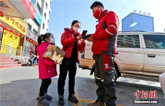 图为湖北籍游客与女儿收到从网上订购的学习网课资料快递。