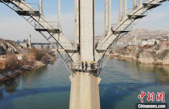 图为职工们在桥中间巡检。 高展 摄
