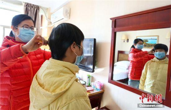 """图为甘肃张掖首批湖北籍游客""""解禁""""第一天,母亲为女儿梳头。"""