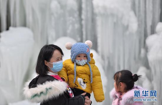 12月26日,游客在大墩峡景区冰瀑前游玩。新华社发(史有东 摄)