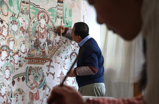 """1月5日,""""敦煌石粉彩绘技艺""""酒泉市级非物质文化遗产代表性传承人王启江和学员在甘肃省敦煌市沙州镇的工作室里,临摹创作敦煌壁画作品。"""