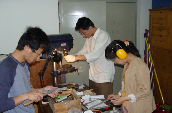 甘恒谦(左一)和同事一起在做接收机的盒子(由受访者提供)