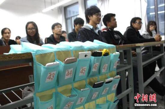 """江苏盐城师范学院城市学院却看到一个""""无手机课堂"""",学生上课前将手机放在教室门口统一的袋子里。"""