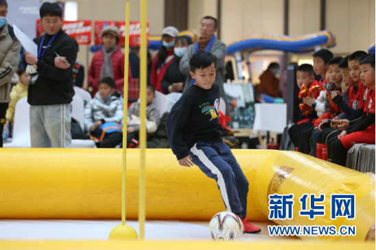 青少年足球技能评测大赛中选手正在过障碍运球。新华网发(童张伟 摄)