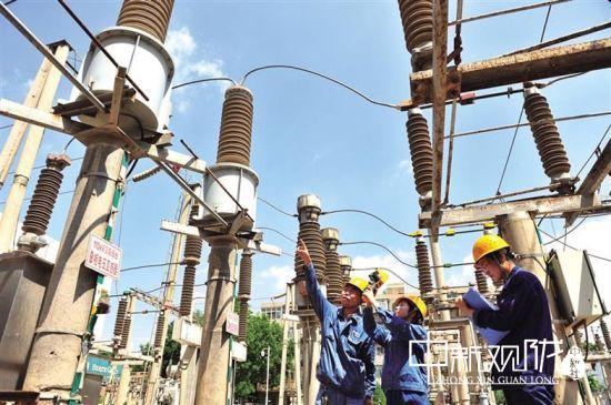 图为工作人员检查电力设备。(资料图)李 昕 摄