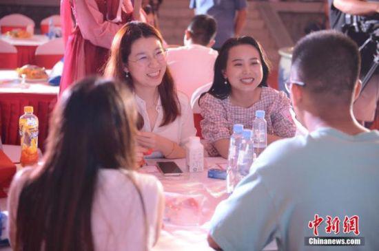 资料图:年轻人在相亲会上交谈。(图文无关) 中新社记者 刘文华 摄