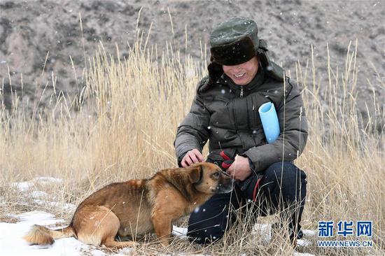 """1月15日,三岔资源管护站护林员冯德俊在巡山途中和""""小黄""""玩耍。"""