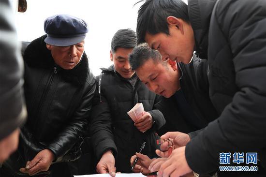1月20日,在元古堆村2019年度企业带动入股分红大会上,村民在签字确认分红。