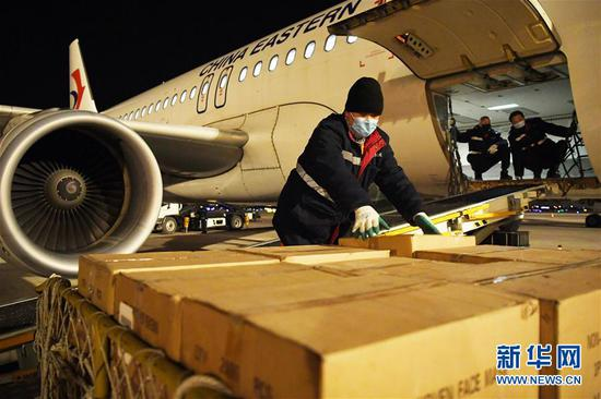 兰州中川国际机场工作人员在停机坪上装卸刚抵达的防控物资(2月3日摄)