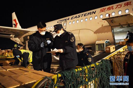 兰州海关工作人员在兰州中川国际机场停机坪上查验刚抵达的防控物资(2月3日摄)