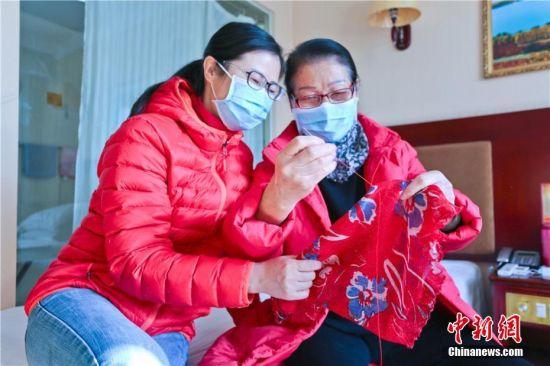 """图为在湖北籍游客在丝巾绣上""""平安、大爱、幸福"""",准备离开时送给张掖人。"""