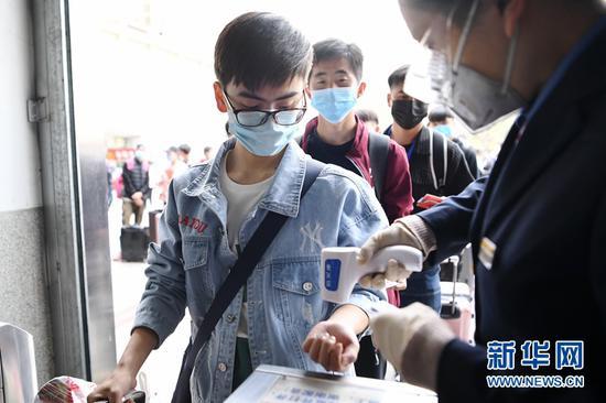 4月17日,塔里木大学的学生在兰州火车站进站口测温后进站。