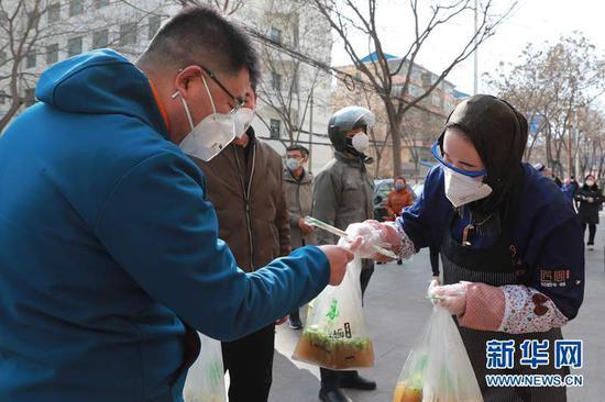 2月19日,在兰州市西固区一家牛肉面馆外,面馆工作人员(右一)将打包好的牛肉面交给取餐市民。