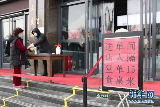 3月18日,在兰州市城关区南滨河东路的一家牛肉面馆,消费者在入店就餐前接受体温检测。