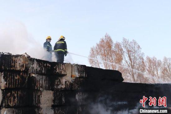 图为消防员冷却保护未燃烧的棉花堆垛,扑灭明火。