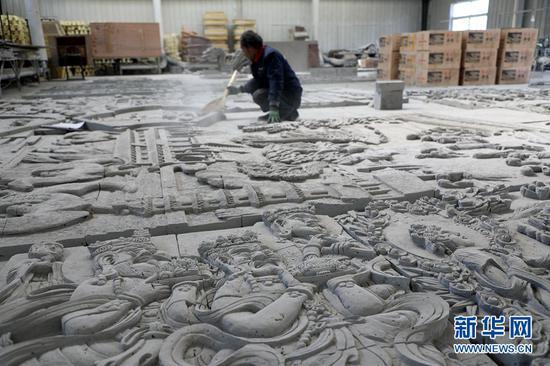 工作人员清理砖雕作品上的粉尘。