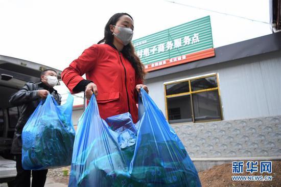 梁倩娟(右)从车上将附近村民送来的农产品卸货(3月8日摄)。新华社记者 陈斌 摄