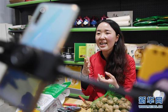 梁倩娟在自己的电商服务点利用网络直播平台展示家乡农产品(3月8日摄)。新华社记者 陈斌 摄