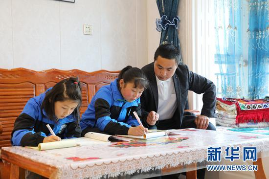 马进龙下班后在县城南区易地扶贫搬迁安置点新家指导孩子写作业