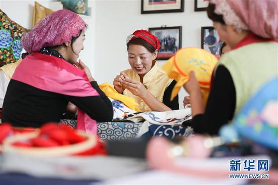 5月30日,在舀水村东乡土本土刺绣工艺扶贫车间,马色麦(中)和绣娘们一起制作绣品。