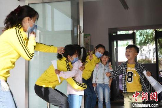 图为幼儿复课,与老师拥抱。