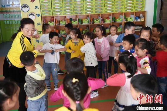 """图为教师史春梅教授幼儿用""""胳膊肘轻挨对方胳膊肘""""的方式表示友好,用寓教于乐的方式将防疫知识贯穿其中。"""