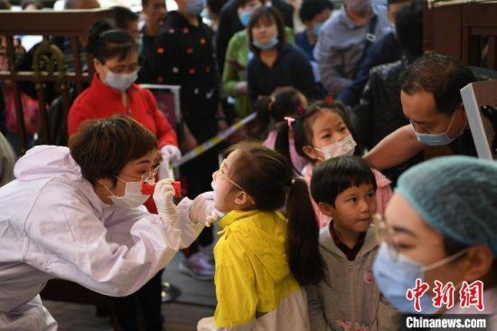 图为幼儿接受校医检查。