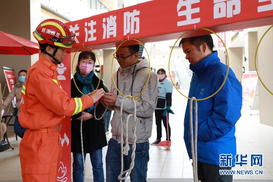 图为消防队员向市民介绍安全绳索。新华网发(童张伟 摄)