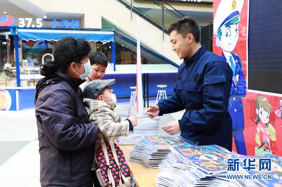 图为消防队员给市民现场赠阅《漫画消防》云图册。新华网发(刘欣瑜 摄)