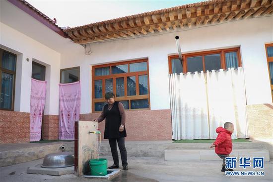 11月9日,布楞沟村村民马麦热在(左)在家中接水。脱贫攻坚工作开展以来,布楞沟村埋设自来水管15公里,建成蓄水池7座,结束了群众吃水靠车拉、驴驮、人背的历史。 新华社记者 马希平 摄