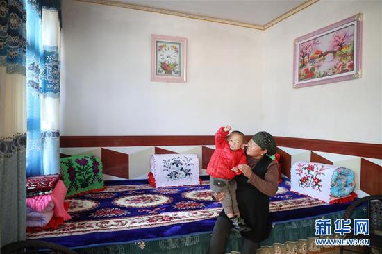 11月9日,布楞沟村村民马麦热在(右)在家中带孙子玩耍。 新华社记者 马希平 摄