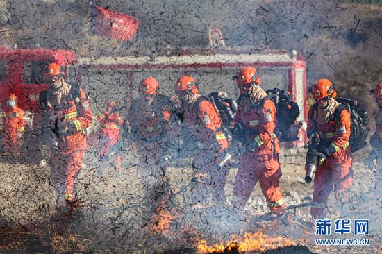 参演指战员正在清理余火。 新华网发 (李艺豪 摄)
