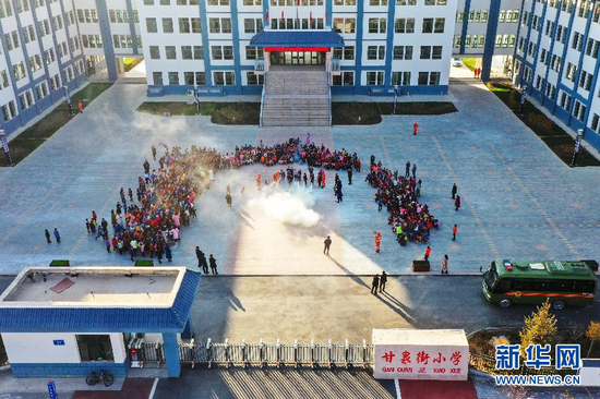 在甘肃省森林消防总队张掖市支队指战员指导下,甘泉街小学学生学习使用干粉灭火器。新华网发 (尤国功 摄)