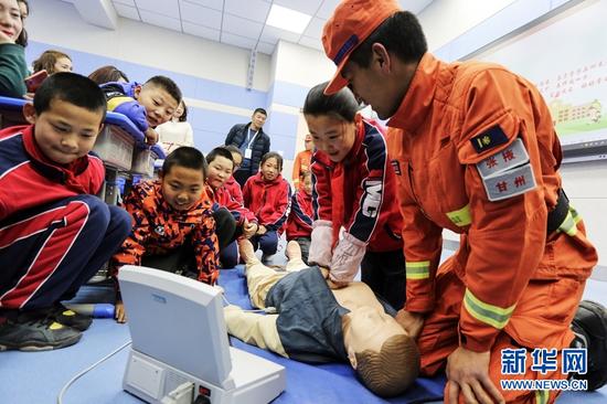 甘肃省森林消防总队张掖市支队指战员在甘泉街小学指导学生进行心肺复苏。新华网发(张小军 摄)